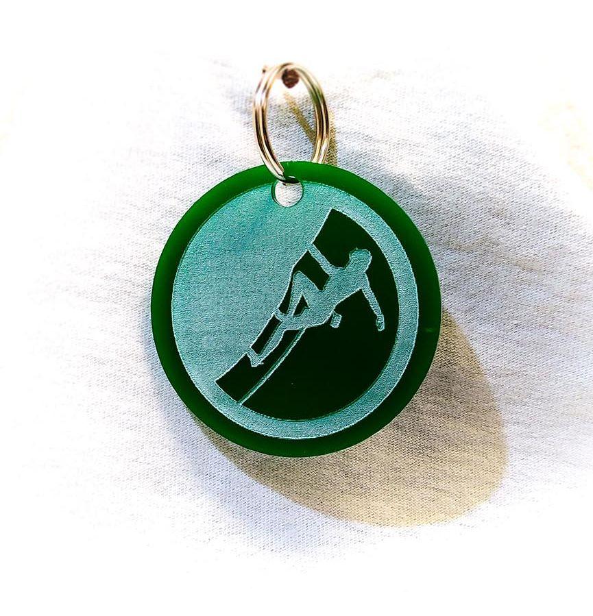 Création gravure porte-clé sur plastique d'un skieur vert