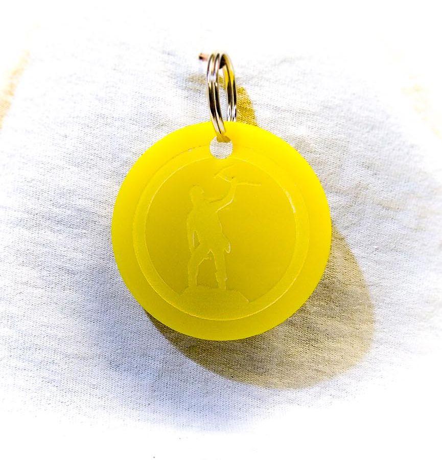 Création gravure porte-clé ovale sur plastique d'un alpiniste jaune