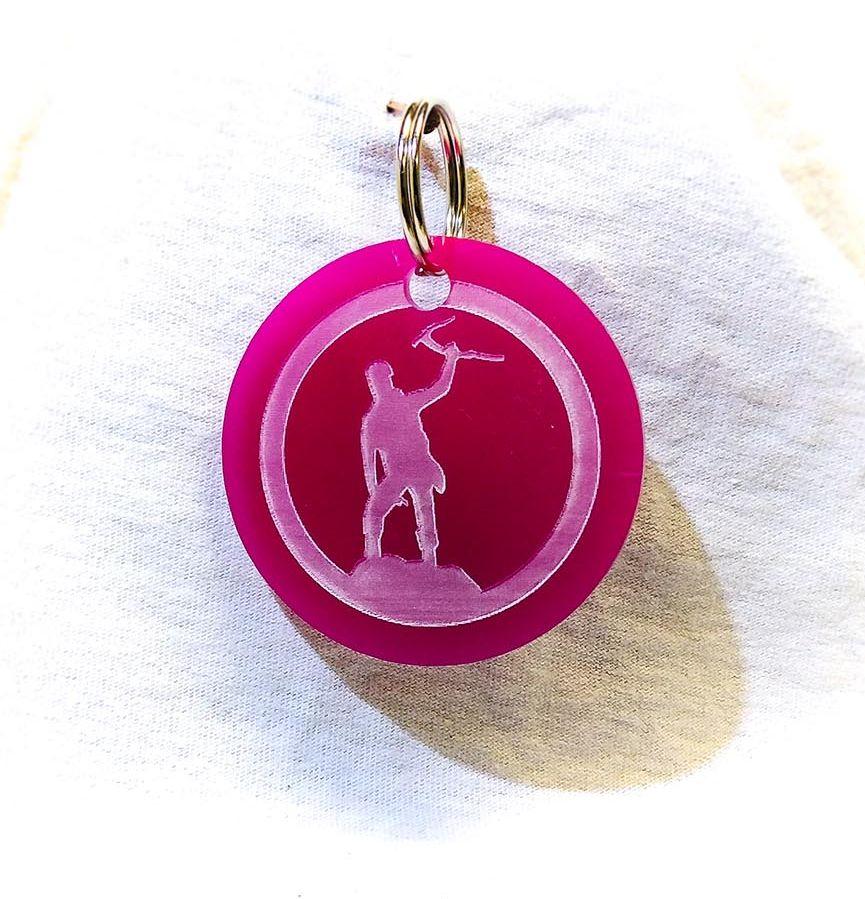 Création gravure porte-clé ovale sur plastique d'un alpiniste rose