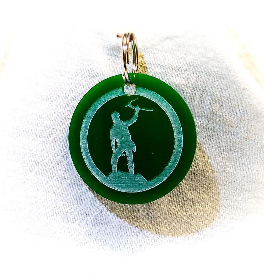 Création gravure porte-clé ovale sur plastique d'un alpiniste vert
